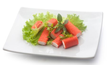 crabmeat: Salad with pieces of red crab stick, fresh lettuce and basil on the white plate