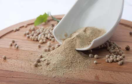 white pepper: Powder and whole seeds of white pepper on the wooden board
