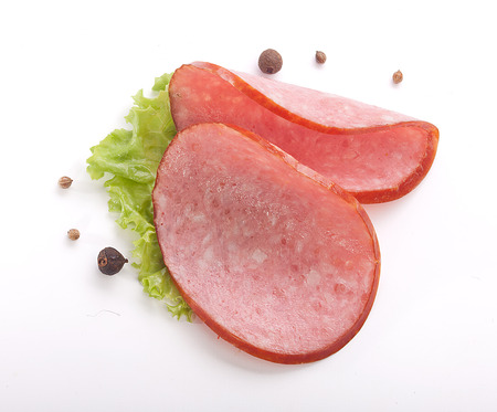 pf: Two pieces pf smoked sausage with fresh green lettuce and black pepper on the white