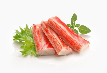 Three red crab stick with green lettuce and basil on the white plate Stock Photo