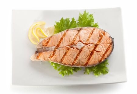 fish plate: Grilled stake of salmon with fresh green lettuce and lemon on the white plate