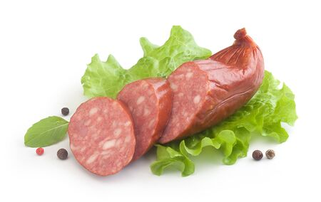 krakow sausage: Some pieces of smoked sausage with fresh green lettuce, basil and black pepper on the white