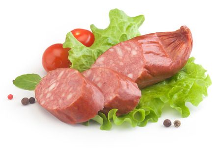 Some pieces of smoked sausage with fresh tomato, lettuce, basil and black pepper on the white