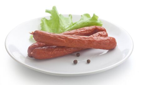 isolated three smoked sausages on the white plate with lettuce and pepper Standard-Bild