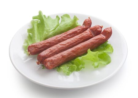 isolated three smoked sausages on the white plate with lettuce