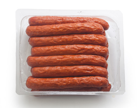 isolated plastic package with smoked sausages on the white