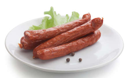 isolated some smoked sausages on the white plate with lettuce and pepper Standard-Bild