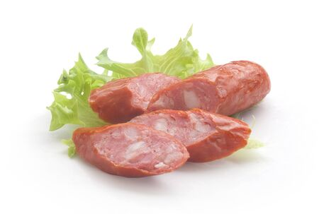 Isolated handful of pieces of smoking sausages with fresh green lettuce