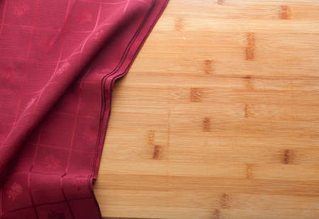 red tablecloth: Folded red tablecloth on the wooden table