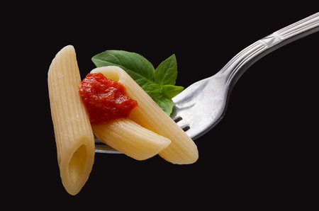 Pasta on the fork on the black background