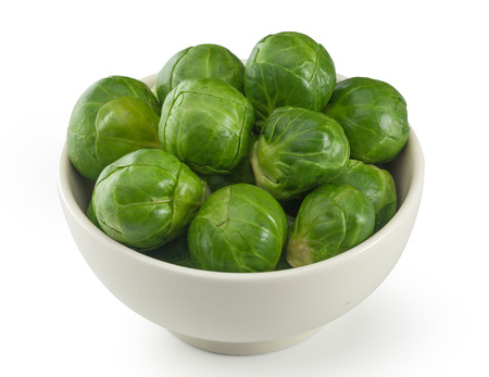 brussels sprouts: Handful of fresh green brussels sprouts in the bowl Stock Photo