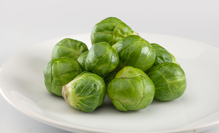 brussels sprouts: Handful of fresh green brussels sprouts on the plate