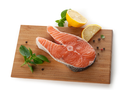 Steak of salmon with fresh basil and lemon on the wooden board Banque d'images