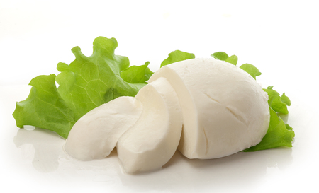 Sliced ball of mozzarella with fresh green lettuce Stock Photo