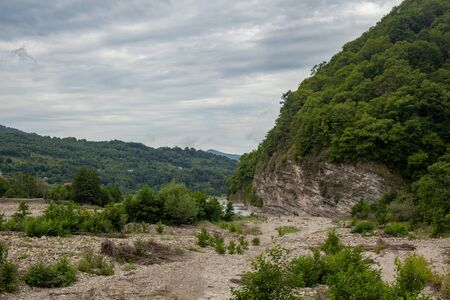 Cloudy summer landscape with a stone bed of the Ashe river