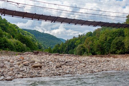 Suspension bridge over the mountain river at the summer cloudy day