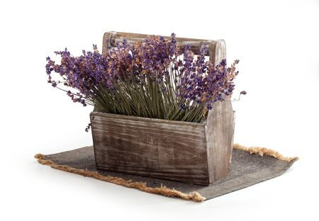 Isolated wooden box with dry lavender flowers on the napkin