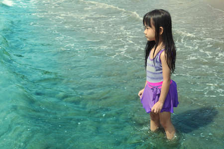 lonelyness: Asian Little Girl Standing at the Beach Facing to the Sea Filling Sad and Alone