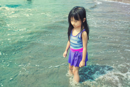 lonelyness: Asian Little Girl Standing at the Beach Facing Sad and Alone