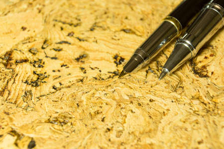 Fountain pen on textured cork table. A textured background.Copy paste place