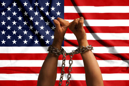 Two hands shackled a metal chain on the background of the USA flag. Stock Photo