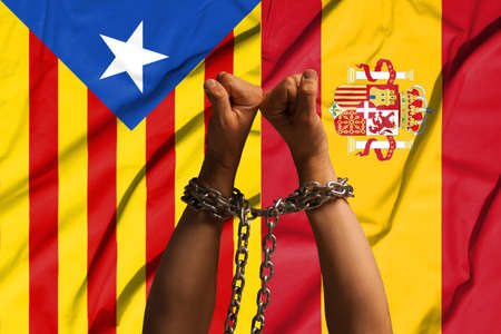 Two hands shackled a metal chain on the background of flags of Catalonia and Spain.