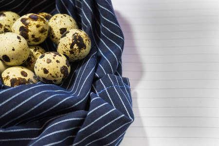 Oeufs de caille sur une serviette sur forme de nid de fond d & # 39 ; un autocollant pour une étiquette Banque d'images - 90299830