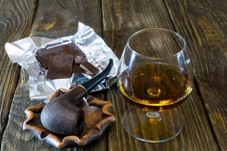Pipe in the ashtray, a glass of cognac and Dark chocolate on a textured oak table