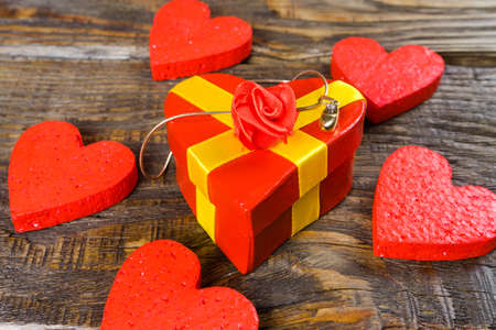 Red gift box in the form of it has shaped pendant wooden slipper with diamond, she stands on a wooden background Stock Photo