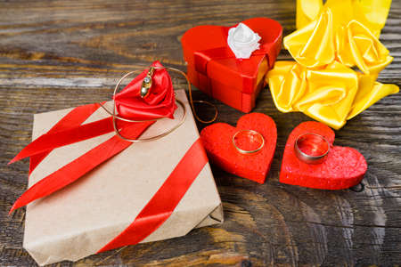The gift is Packed in Kraft paper and tied with a red ribbon with a rose in the center of which lies a pendant in the shape of clogs with briliant. Stock Photo
