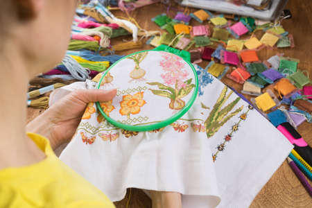 Girl sitting at a table where everything is necessary for embroidery, embroiders a big picture. Copy paste.