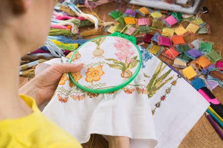 Dziewczyna siedząca przy stole, na którym wszystko jest potrzebne do haftu, wyszywa duży obrazek. Kopiuj wklej.