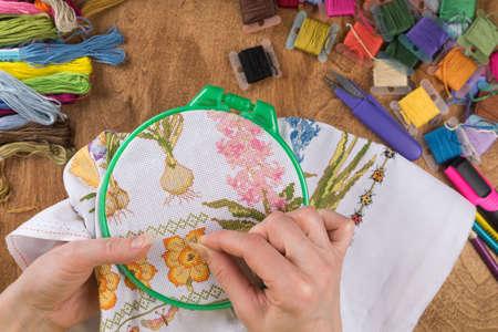 Mädchen sitzt an einem Tisch, wo alles für die Stickerei notwendig ist, stickt ein großes Bild. Kopieren Einfügen. Standard-Bild