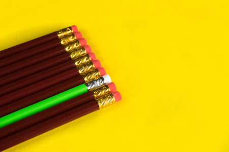 Business concept - lot of same pencils and one different pencil on yellow paper background. Copy paste Stockfoto
