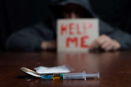 A drug addict at the table holding a sign for help, in front of him a syringe of drugs. Copy paste.
