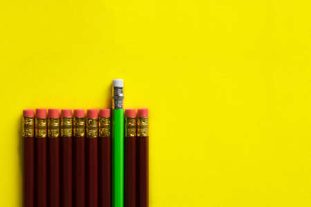 Business concept - lot of same pencils and one different pencil on yellow paper background. Copy paste Stock Photo