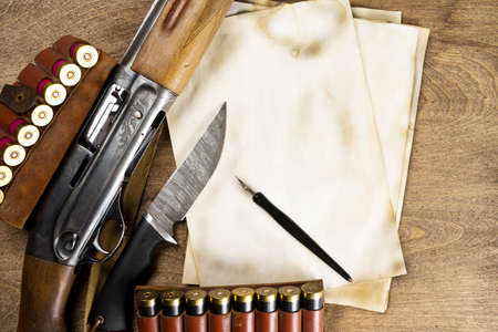 Hunting weapons, ammunition, old sheets of paper, write on them his story. Copy space. Mock up Standard-Bild