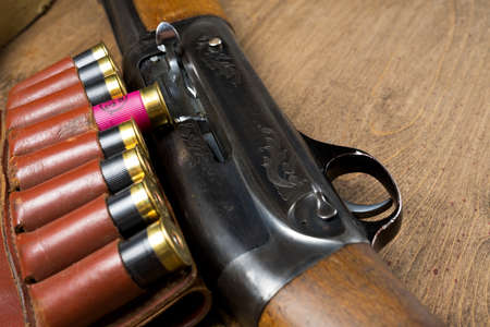 Hunting rifle and ammunition lie on a wooden background