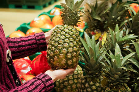 Woman chooses pineapple in a supermarket. Banque d'images