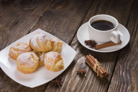 Delicious eclairs sprinkled with icing sugar, stand on a wooden table.