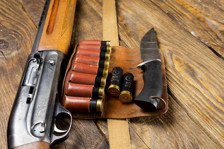 Jagdgewehr und Munition liegen auf hölzernem Hintergrund. Speicherplatz kopieren