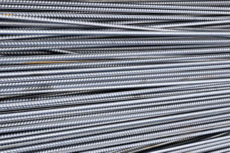 Stack of heavy metal reinforcement bars with periodic profile texture. Close up steel construction armature. Abstract industrial background concept. Copy space for text