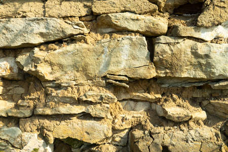 Background texture, stone buds, limestone, basalt, cobblestone, granite, pebbles, slate, sandstone laid the wall or in the fence close up for inscriptions or advertisements