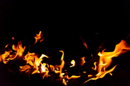Flames of fire from burning coals in the grill late at night. Copyspace for text. Stock Photo