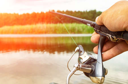 A hand holding a fishing rod. Fishing activity. Copy space.