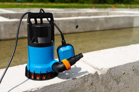 Submersible pump dewater construction site, pumping flood water sing deep well. Copy paste 写真素材