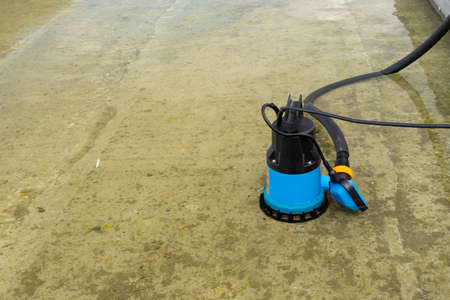 Submersible pump dewater construction site, pumping flood water sing deep well. Copy paste Stock Photo
