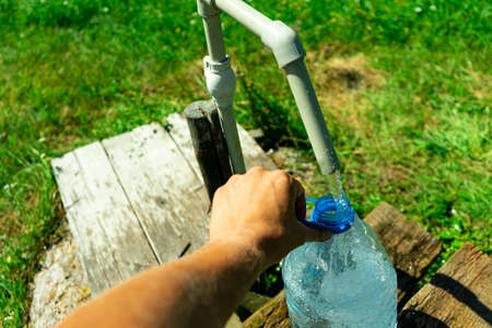 A person collects water in a container.