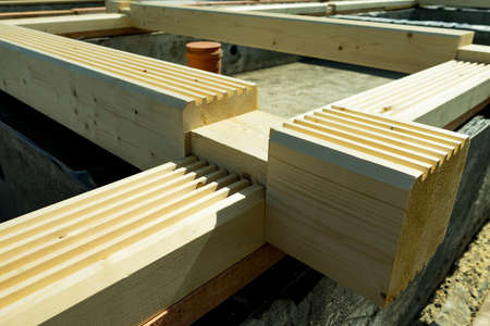 Construction of a wooden house made of profiled laminated veneer lumber.