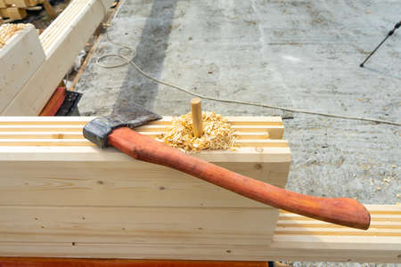 Construction of the house from a bar. Drilling holes and clogging of dowels. Фото со стока